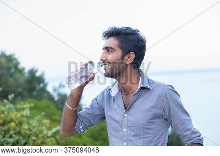 Hydrate Yourself. Man Smiling In Profile About To Drink From A Bottle Of Water Isolated Nature Trees