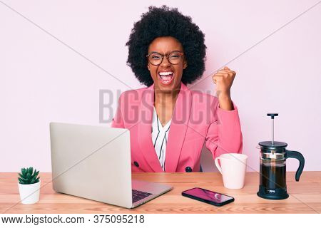 Young african american woman working at desk using computer laptop screaming proud, celebrating victory and success very excited with raised arms