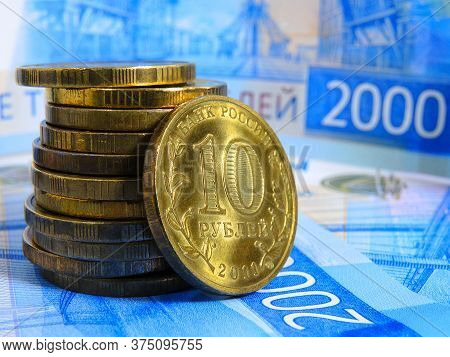 A Stack Of Russian Coins Of 10 Rubles Is In Front Of A Banknote Of 2000 Rubles. Close Up