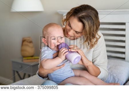 Mother holding and feeding hungry baby from milk bottle. Portrait of crying newborn baby being fed by his mom using bottle. Loving woman giving to drink milk to her crying son.