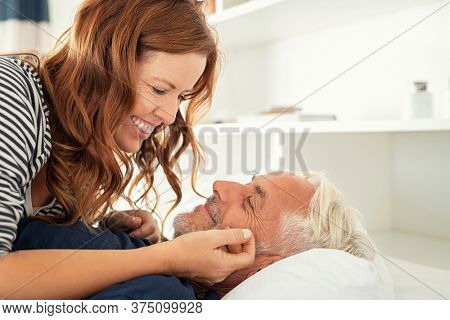 Middle aged lovely woman lying on happy senior man and caresses him. Handsome old man and attractive woman enjoying spending time together while lying in bed. Mature smiling couple in love, copy space