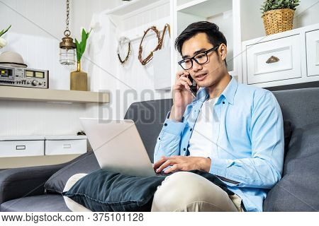 Asian Businessman Is Sitting On The Sofa In His Own House Taking A Call On His Mobile Phone Checking