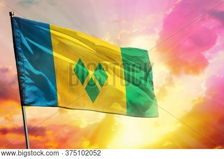 Fluttering Saint Vincent And The Grenadines Flag On Beautiful Colorful Sunset Or Sunrise Background.
