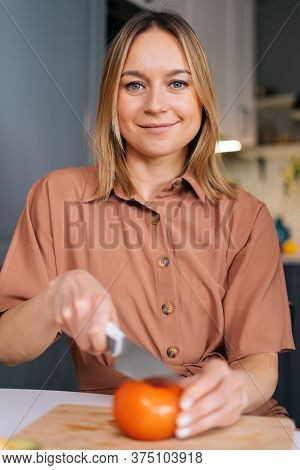 Young Woman Cutting Fresh Tomato Using Kitchen Knife On Wooden Cutting Board, Looking At Camera. You