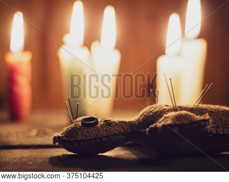 Rag Doll Voodoo Pierced With Needles, Lying On A Wooden Table Surrounded By Burning Candles, Close-u