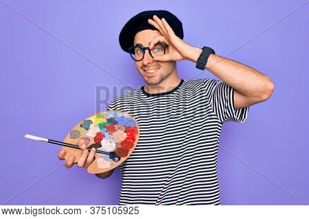 Young artist man with blue eyes wearing french beret and glasses drawing using paintbrush with happy face smiling doing ok sign with hand on eye looking through fingers