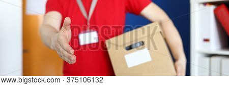 Close-up Of Male Deliverer Holding Cardboard And Shake Hand. Man In Bright Red Shirt With Name Tag.