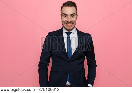 enthusiastic elegant guy in suit holding hands in pockets and smiling, standing on pink background