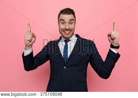 enthusiastic young elegant man pointing fingers up and smiling, standing on pink background