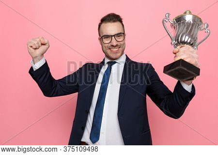 happy enthusiastic guy in suit wearing glasses, holding fist and trophy in the air and celebrating victory, smiling and standing on pink background