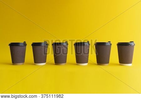 Closeup At Six Takeaway Paper Coffee Cups With Plastic Covers, One Cup Differs From Others, Yellow B