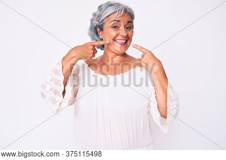 Senior hispanic grey- haired woman wearing casual clothes smiling cheerful showing and pointing with fingers teeth and mouth. dental health concept.
