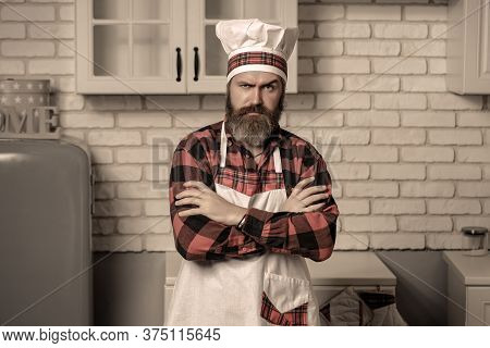 Handsome Bearded Cook Chef In White Uniform And Hat With Long Lush Moustache On Serious Face Standin