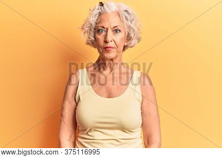 Senior grey-haired woman wearing casual clothes relaxed with serious expression on face. simple and natural looking at the camera.