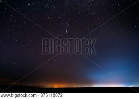 Night Starry Sky With Glowing Stars Above Countryside Landscape. Rural Field Meadow In Early Spring.