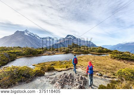 Hiking couple walking on adventure hike at Routeburn Track during sunny day. Hikers carrying backpacks tramping on Key Summit Track. People on vacation at Fiordland National Park, New Zealand.