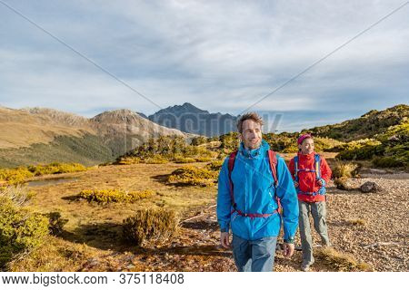 Young hiking couple walking at Routeburn Track during sunny day. Hikers are carrying backpacks while tramping on Key Summit Track. They are on vacation at Fiordland National Park in New Zealand.
