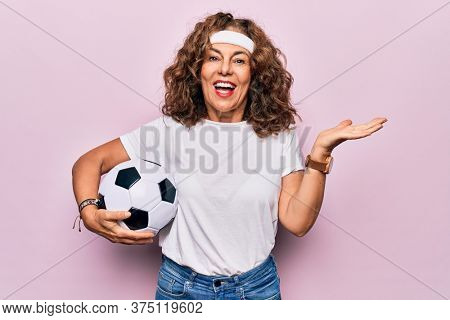 Middle age beautiful sporty woman playing soccer holding football bal over pink background celebrating achievement with happy smile and winner expression with raised hand