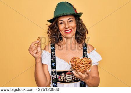 Middle age woman wearing traditional octoberfest dress holding bowl with baked pretzels with a happy face standing and smiling with a confident smile showing teeth
