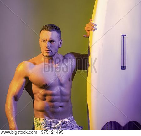 Close-up Portrait Of Sexy Very Handsome Tanned Young Man In Shorts And Fit Naked Torso With A Surfbo