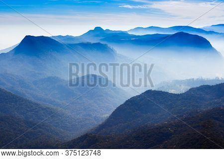 Foggy Mountains Aerial Panoramic View From The Adams Peak Or Sri Pada On Sunrise. Adams Peak Is A Ta