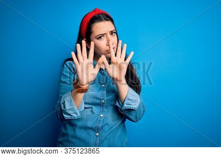 Young brunette woman wearing casual denim shirt over blue isolated background Moving away hands palms showing refusal and denial with afraid and disgusting expression. Stop and forbidden.