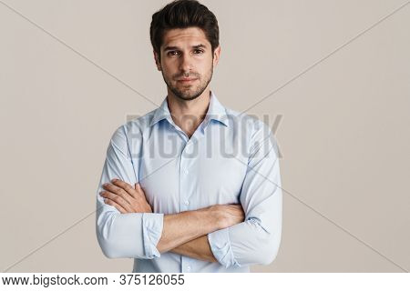 Portrait of unshaven confident man posing and looking at camera isolated over white background