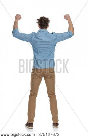 back view of enthusiastic man in denim shirt holding arms in the air and celebrating, isolated on white background, full body
