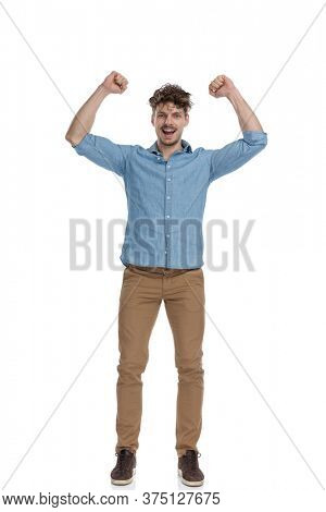 enthusiastic young casual man holding hands in the air and celebrating, smiling and standing isolated on white background, full body
