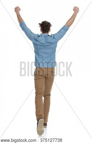 back view of enthusiastic guy holding arms in the air and cheering, walking isolated on white background, full body