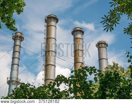 Chimneys Of A Thermal Power Plant Against Blue Sky. Power Station In Bucharest.