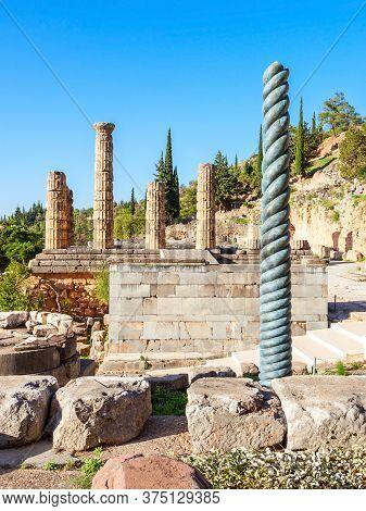 Serpent Column Of Plataea And Temple Of Apollo In Delphi. Delphi Is Ancient Sanctuary That Grew Rich