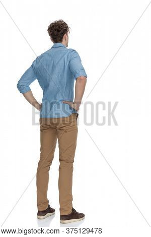 back view of concerned casual guy holding hands on hips and thinking, standing isolated on white background, full body