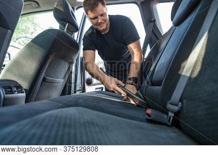Man Cleaning Inside Car With Vacuum Cleaner