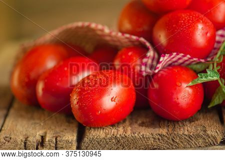 Long Plum Tomatoes With Checkered Red Napkin On Wooden Table. Heap Of Fresh Tomatoes