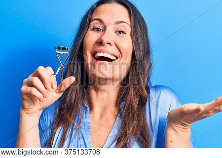 Young beautiful brunette woman holding eyelash curler over isolated blue background celebrating achievement with happy smile and winner expression with raised hand