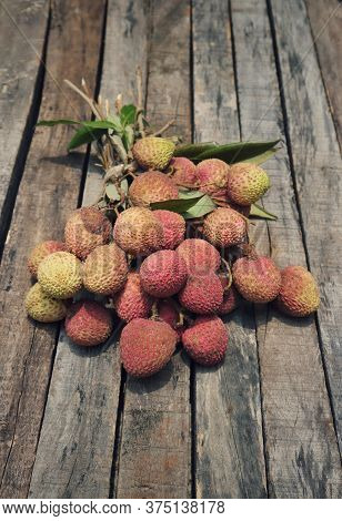 Organic Lychee Or Litchi Cluster With Leaves Isolated On Wooden Background In Vertical Orientation