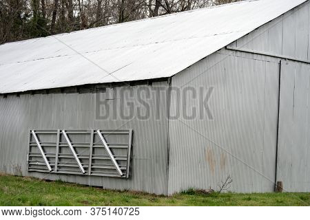 A Tin Barn Shines Brightly In The Sunlight On A Farm In Missouri. A Portable Metal Gate Hangs On The