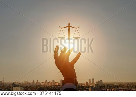 Concepts Of Justice And Jurisdiction In A City.hand Shows Scales Of Justice Against The Backdrop Of