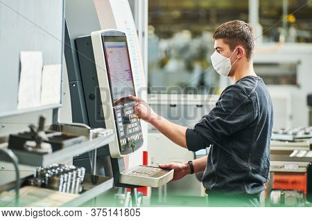 Industrial worker operating cnc machine in protective mask at metal machining industry