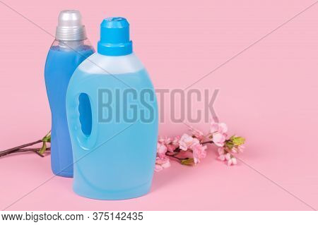 Bottles Of Detergent And Fabric Softener On Pink Background With Flowers. Containers Of Cleaning Pro