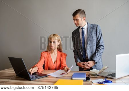 A Business Woman And Man At A Wooden Office Desk  Working At The Project On The Paper And Computer,