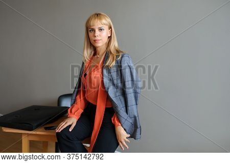 A Business Woman On The Office Desk In A Grey Jacket, Grey Background