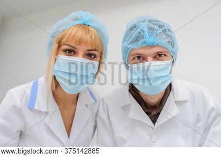 Two Doctors With Masck  In A Medical Office, Close View