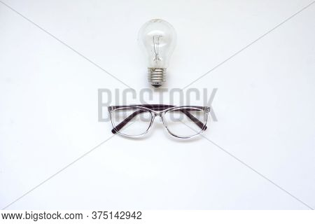 A Pair Of Glasses And A Light Bulb, Close View, Whit Background