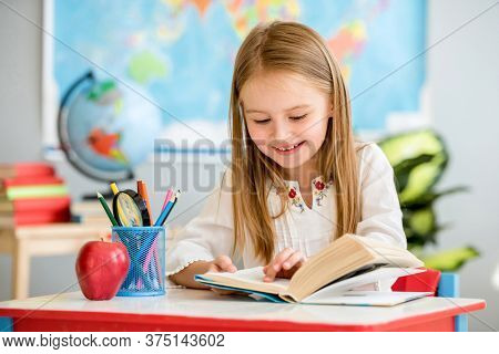 Little pretty blond girl sitting in the classroom at the white desk and attentively reading book