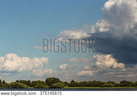 Clouds Above The Earth. Picturesque Clouds In The Sky Backlit By The Sun.
