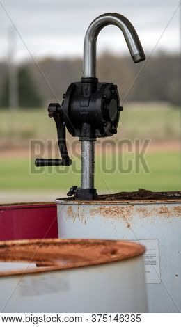 A Defocused Foreground And Background Draws The Eye To The Hand Crank Pump On The Rusty Barrel Of Ol