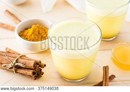 Detox Drink. Golden Milk With Turmeric And Cinnamon In A Transparent Glass On A Wooden Table