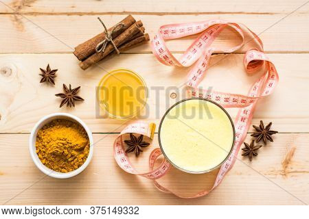 Detox Drink. Golden Milk With Turmeric And Cinnamon In Glasses And A Measuring Tape On A Wooden Tabl